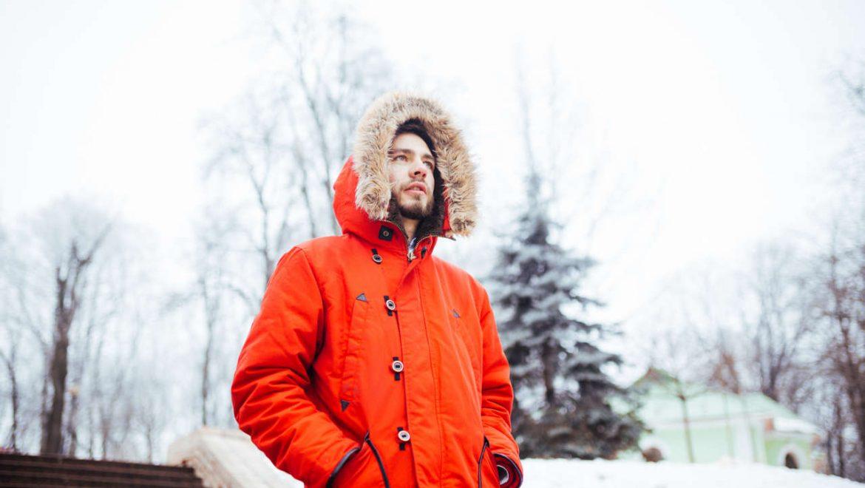 Mężczyzna w modnej pomarańczowej kurtce zimowej